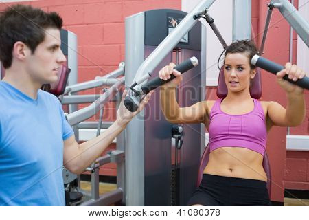 Male trainer helping woman on weights machine in gym