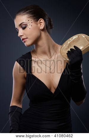 Beauty dressed for elegant party posing in black dress with golden party handbag and gloves, glamorous makeup with strasses.