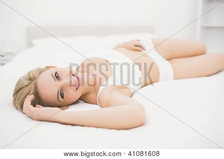 Portrait of smiling young woman in undergarments lying in bed at home