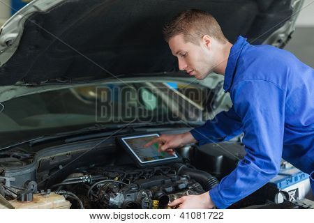 Male mechanic using tablet pc while examining car engine