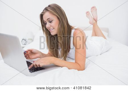 Smiling woman buying on website with her credit card