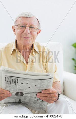 Smiling elderly man reading the news in the living room
