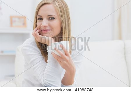 Portrait of young woman with tea cup sitting on couch at home