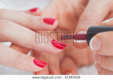 Details shot of hands applying red nail varnish to finger nails at nail salon