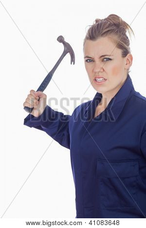 Portrait of an angry female mechanic holding claw hammer against white background
