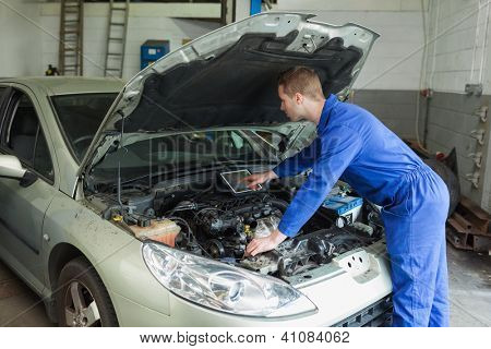 Male mechanic examining car engine with the help of digital tablet