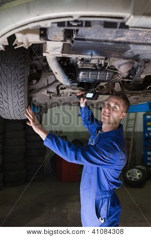 Portrait of male mechanic examining car in workshop