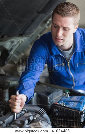 Young male mechanic working on car engine