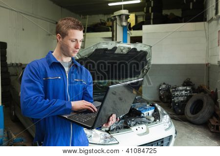 Male mechanic using laptop in garage with car in background