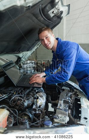 Portrait of repairman using laptop on car engine