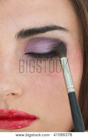 Brunette with red lips getting eye shadow applied