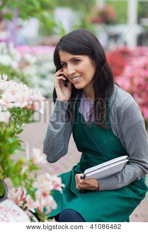 Employee doing stocktaking while calling in the garden center kneeling down