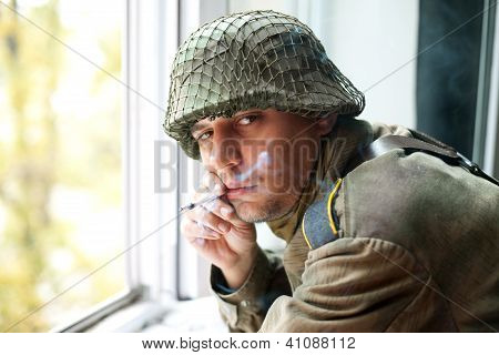 Soldier Smoking Near Window