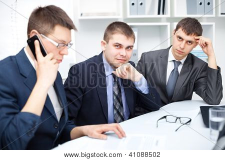 Team Of Young Business Men Working Together At Office , One Of Them Talking On A Cell Phone