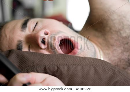 Man Yawning In Bed