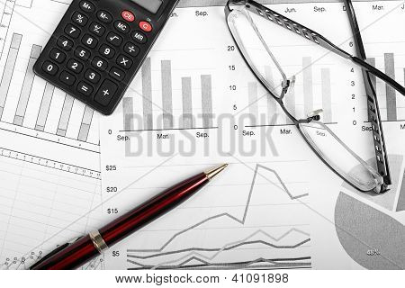 Business Finance Charts With Pen, Glasses And Calculator