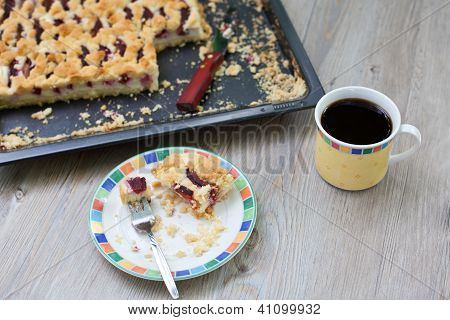Fresh baked plum pie and cup of coffee on wooden table