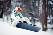 picture of snowboarding  - Young beautiful woman adjusts her bindings on snowboard sitting at ski slope - JPG