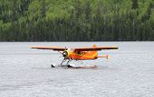 foto of hydroplanes  - little orange hydroplane on a wild lake - JPG