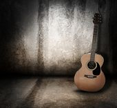 image of string instrument  - An wooden acoustic guitar is against a grunge textured wall - JPG