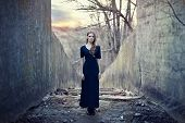 stock photo of gothic  - beautiful lonely girl in long dress near gloomy tunnel on sunset - JPG