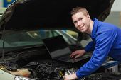 Portrait of male mechanic using laptop while repairing car