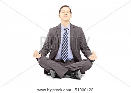 Young businessman in suit sitting on a floor and meditating isolated on white background
