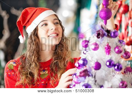 Beautiful female owner in Santa hat smiling while decorating Christmas tree at store