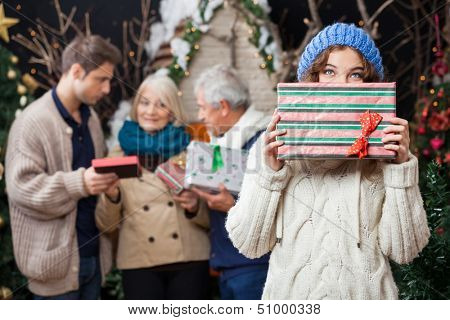 Portrait of thoughtful young woman holding Christmas present with family standing in background at store