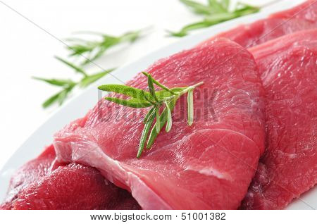 closeup of some raw beef fillets on a plate on a white background