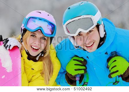 Skiing, winter sports - portrait of young skiers, couple having fun on ski