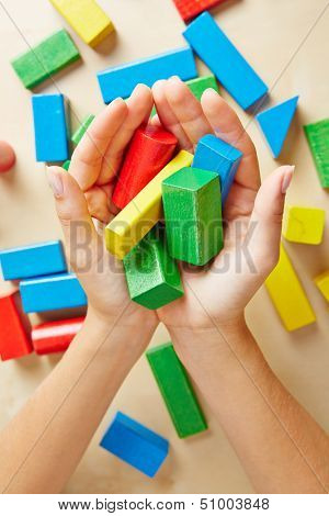 Two hands holding many colorful wooden building blocks