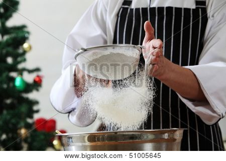 caster sugar sifting through a sieve for a baking