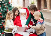 Children and Santa Claus reading book against Christmas tree in courtyard