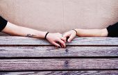 image of sitting a bench  - two people holding hands on a bench - JPG
