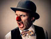 stock photo of bowler  - portrait of a clown with a bowler hat grimacing - JPG
