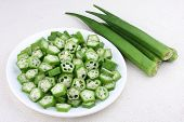 stock photo of okra  - Okra sliced in to cross section with fresh raw okras - JPG