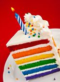 stock photo of sprinkling  - Slice of fun rainbow layered birthday cake decorated with sprinkles and buttercream icing with lit birthday Candle over a red background - JPG