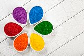 stock photo of jimmy  - A rainbow assortment of colorful baking sprinkles used for decorating cookies and cakes in petal shaped bowls - JPG