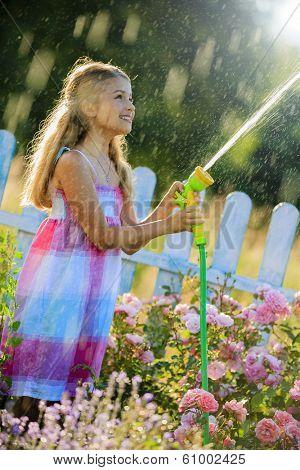 Watering, flower garden - beautiful girl watering roses with garden hose in the garden
