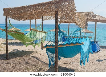 Two hammocks on the sandy beach with umbrellas and sea in the background