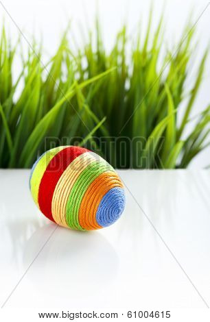 Easter egg covered with colorful woolen yarn. Green grass in background. Space for text