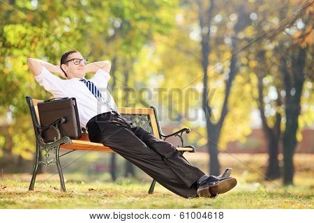 Young businessman taking a break after work seated on a bench in park