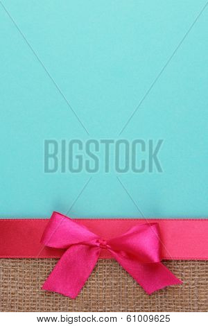 Sackcloth with color ribbon and bow on color paper background