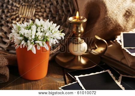 Composition with beautiful snowdrops in vase, candle, old letters and photos on wooden table on sackcloth background