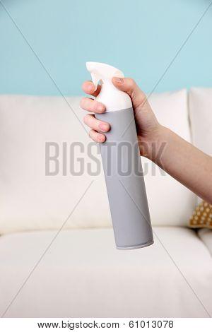 Sprayed air freshener in hand on sofa background