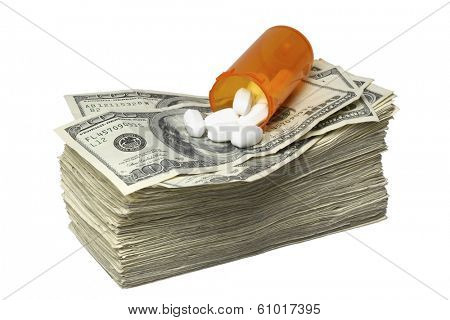 Pills and pill bottle on top of stack of one hundred dollar bills on white backgroud