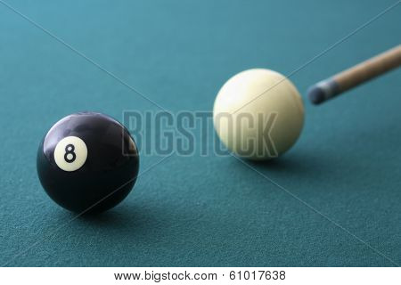 Eight ball and cue ball on green pool table