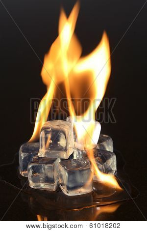 Ice cubes and fire on black background
