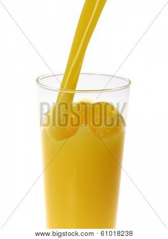 Orange juice pouring into tall glass on white background